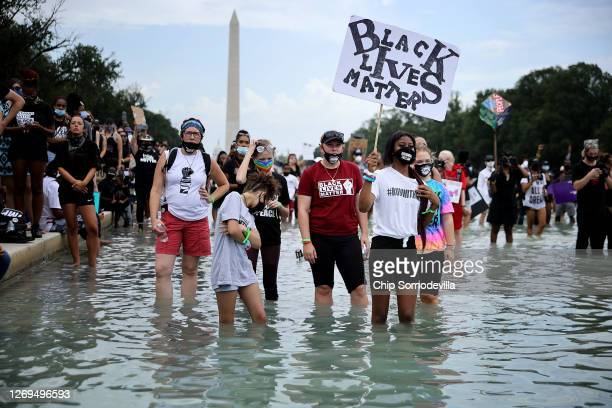 People stand in the Reflecting Pool along the National Mall as they rally near the Lincoln Memorial during the March on Washington August 28, 2020 in...