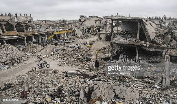 People stand in the rubble of buildings destroyed in the clashes between DAESH militants and Kurdish armed armed groups in the center of the Syrian...