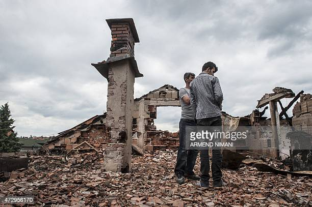 People stand in the rubble of damaged houses after fighting between Macedonian police and an armed group in the town of Kumanovo on May 11 2015...