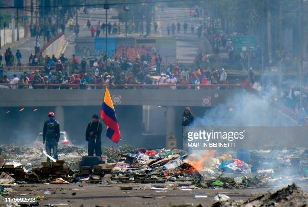 People stand in the street amid the rubble, following a 10-day protest over a fuel price hike ordered by the government to secure an IMF loan, in...