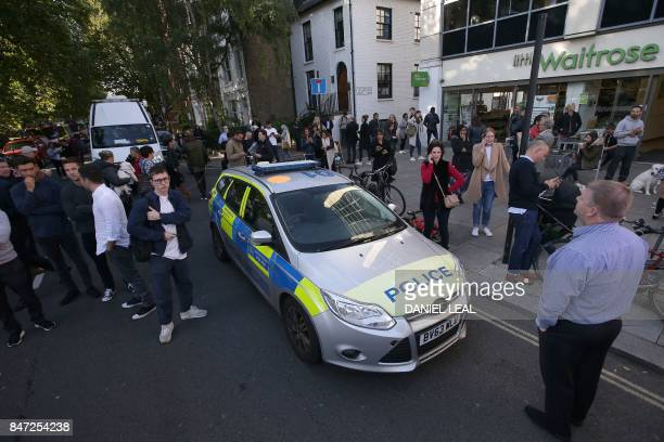 People stand in the street by a Police car close to Parsons Green underground tube station in west London on September 15 following an incident on an...