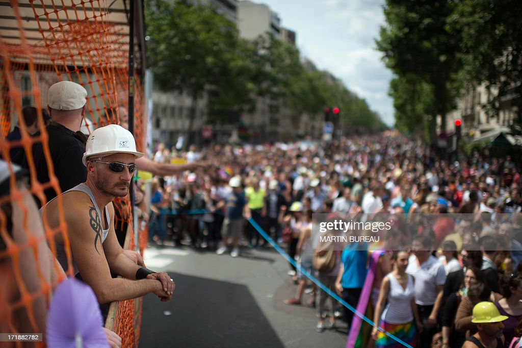 People stand in the streets as a truck with demonstratours parades during the homosexual, lesbian, bisexual and transgender (HLBT) visibility march, the Gay Pride, on June 29, 2013 in Paris, exactly one month to the day since France celebrated its first gay marriage.