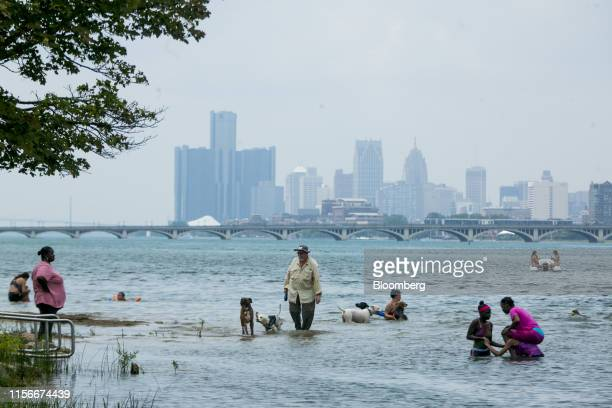 People stand in the water at a beach on Belle Isle in Detroit Michigan US on Friday July 19 2019 The forecast for this weekend shows the heat index...