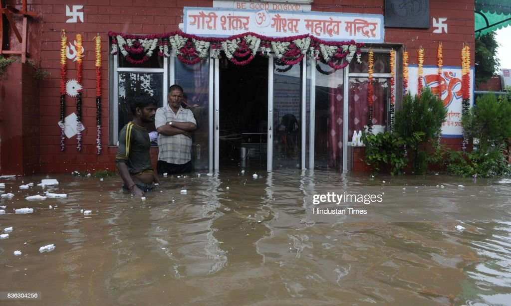 People stand in thigh deep water at Gaushala at Sector 45 after heavy rains on August 21 2017 in Chandigarh India Heavy rainfall on morning brought...