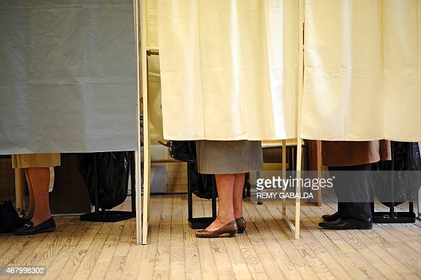People stand in voting booths on March 29 2015 during the second round of the French departemental elections in the southwestern French city of...