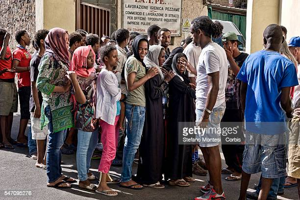 People stand inline to take the ticket to eat during the humanitarian support is provided for migrants in via Cupa on July 11 2016 in Rome Italy...