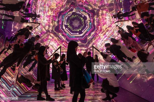 TOPSHOT People stand inside a kaleidoscope installation erected as part of Christmas festivities at a shopping arcade in Hong Kong on December 25 2018