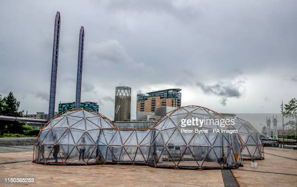 People stand inside Pollution Pods installed by Cleanairgmcom at MediaCityUK in Manchester People can experience the air quality of cities across the...
