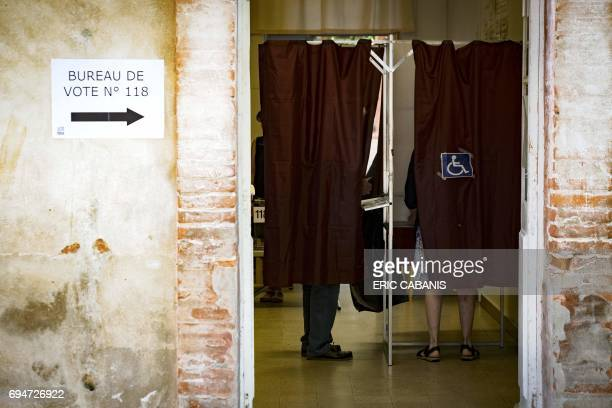 People stand inside voting booths at a polling station in Toulouse during the first round of the French legislative elections on June 11 2017 / AFP...