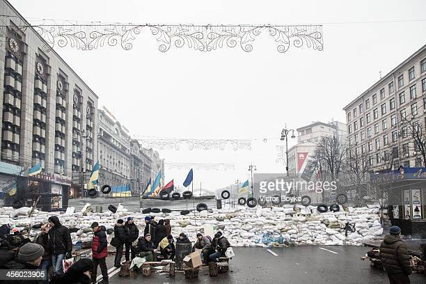 People stand near a barricade on Khreshchatyk street near Maidan Square on December 12 2013 in Kiev Ukraine Thousands have been protesting against...