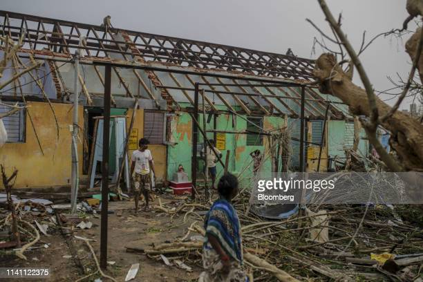 People stand near a damaged home after Cyclone Fani passed through Puri Odisha India on Saturday May 4 2019 A category 4 storm with strong wind and...