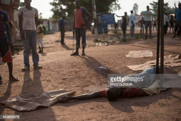 People stand near a dead body in a street of the Combattant neighborhood in Bangui in Central African Republic on December 10 2013 French President...