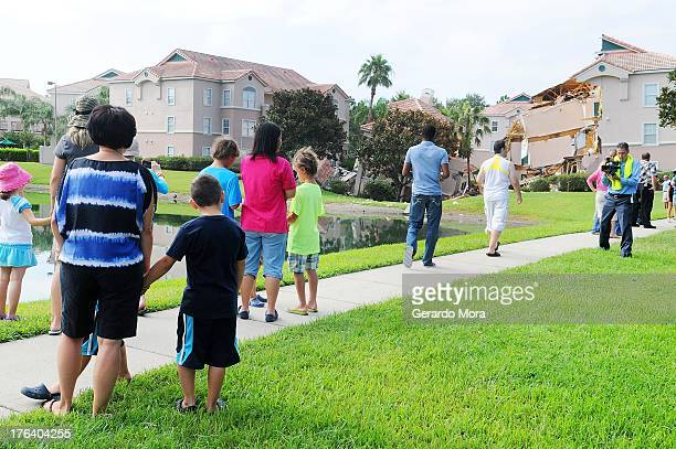 People stand near a partially collapsed building over a sinkhole at Summer Bay Resort near Disney World on August 12 2013 in Clermont Florida The 40...