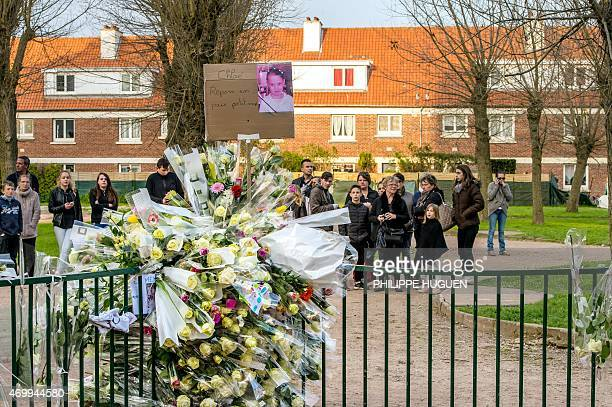 People stand near a playground as they gather in homage to Chloe a nineyearold girl who was killed a day before on April 16 2015 in Calais northern...