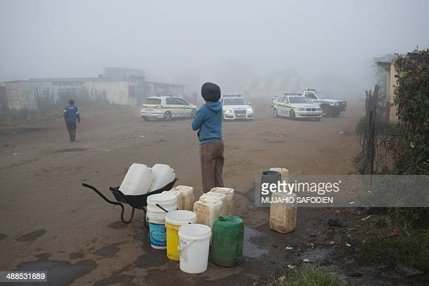People stand near a polling station guarded by police forces on May 7 2014 in Gugulethu South Africans vote in their fifth democratic elections on...