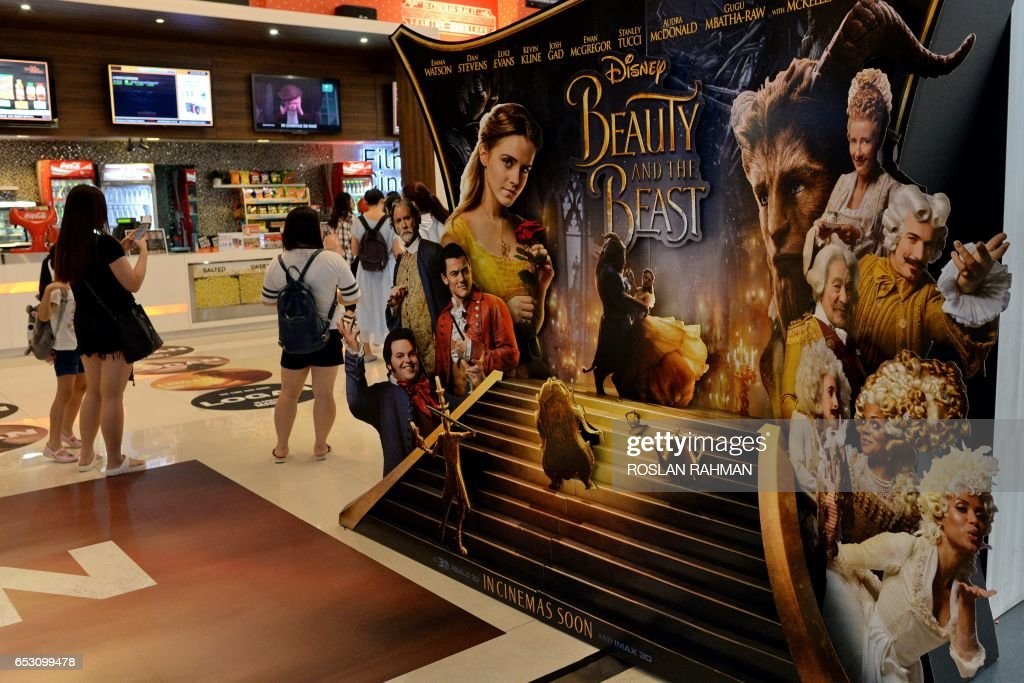 People stand near a promotional display for the film 'Beauty and the Beast' at a cinema in Singapore on March 14, 2017. The film has come under fire from religious figures in Singapore, with Christian clergy attacking Disney for deviating from 'wholesome, mainstream values'. / AFP PHOTO / Roslan RAHMAN
