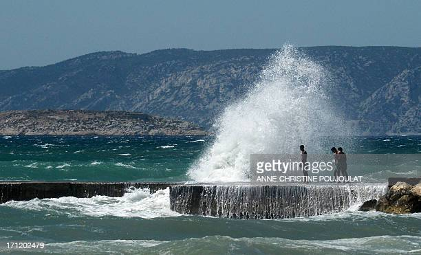 People stand near a wave crashing off Prado beach in Marseille southern France as a strong mistral wind blows on June 23 2013 AFP PHOTO /...