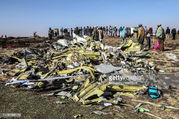 TOPSHOT People stand near collected debris at the crash site of Ethiopia Airlines near Bishoftu a town some 60 kilometres southeast of Addis Ababa...