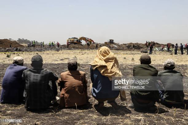 People stand near collected debris at the crash site of Ethiopia Airlines near Bishoftu a town some 60 kilometres southeast of Addis Ababa Ethiopia...