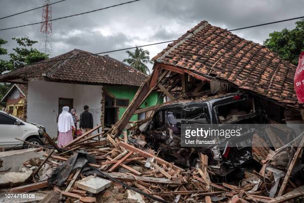 People stand near destroyed houses after hit by tsunami as they looking for their belonging at a on December 24 2018 in Carita Banten province...