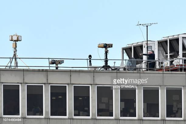 People stand near equipment on the rooftop of a building at London Gatwick Airport south of London on December 21 as flights resumed following the...