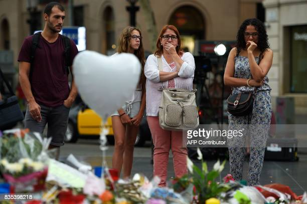People stand near flowers candles and tributes to the victims of the Barcelona attack on the Las Ramblas boulevard in Barcelona on August 19 two days...