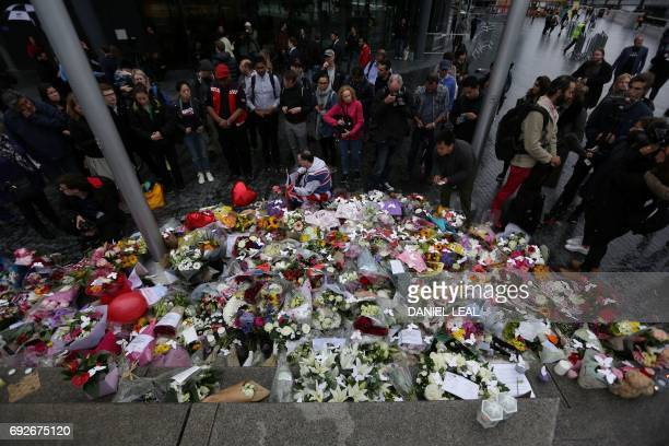 People stand near flowers layed at Potters Fields Park in London on June 5 during a vigil to commemorate the victims of the terror attack on London...