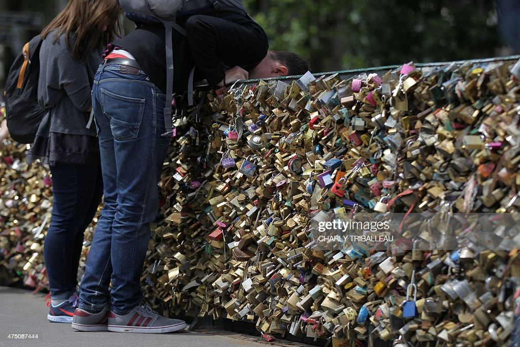 People stand near padlocks hanging on the 'Pont Notre-Dame' on May 29, 2015 in Paris as the Paris municipalty announced that the bridge's fences have to be removed due to the weight of the padlocks put by tourists to ensure everlasting love.