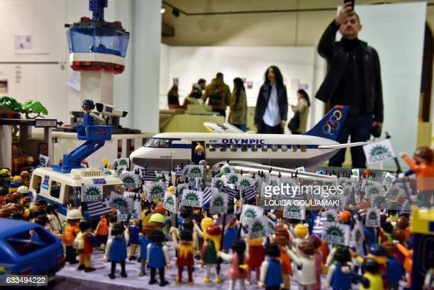 People stand near playmobil models depicting a political rally on the arrival of Andreas Papandreou in Athens during the opening of the exhibition GR...