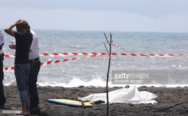 People stand near the body of a bodyboarder killed by a shark covered by a white cloth next to his bodyboard enclosed in a security cordon on...