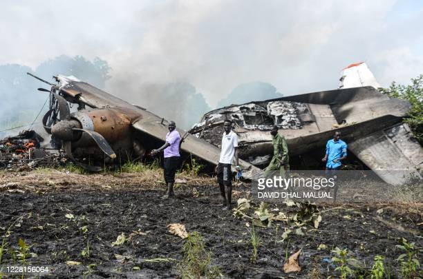 People stand near the cargo plane belonging to a local operator that crashed seven kilometres west of the Juba International airport shortly after...