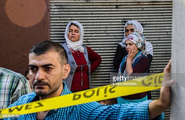 People stand near the explosion scene following a late night attack on a wedding party that left at least 30 dead in Gaziantep in southeastern Turkey...