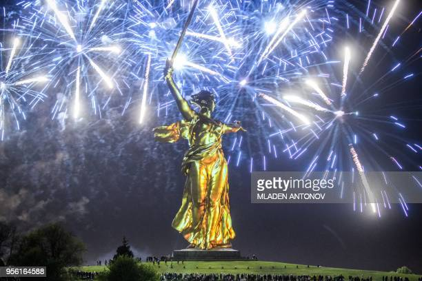People stand near The Motherland Calls statue at the Mamayev Kurgan Memorial Complex in Volgograd, on May 8, 2018 during fireworks for the 73rd...