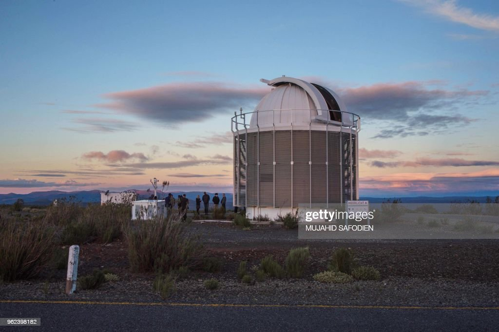 People stand near the new telescope MeerLICHT at the South