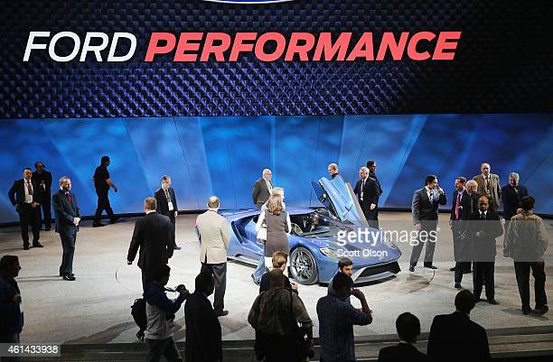 People stand near the newly introduced Ford GT at the North American International Auto Show on January 12, 2015 in Detroit, Michigan. More than 5000...