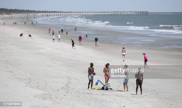 People stand near the ocean in Cherry Grove Beach South Carolina US on Wednesday April 22 2020 Governor Henry McMaster said he was forming an...