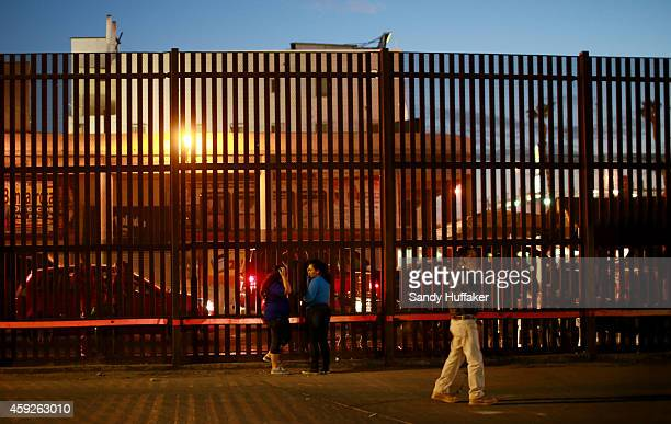 People stand near the US Mexico border wall on November 19 2014 in Calexico California US President Barack Obama plans to announce executive action...