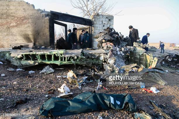 TOPSHOT People stand near the wreckage after a Ukrainian plane carrying 176 passengers crashed near Imam Khomeini airport in Tehran on January 8 2020...