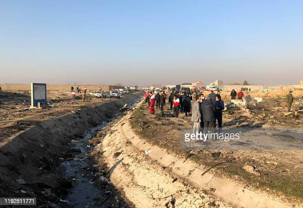 People stand near the wreckage after a Ukrainian plane carrying 176 passengers crashed near Imam Khomeini airport in the Iranian capital Tehran early...