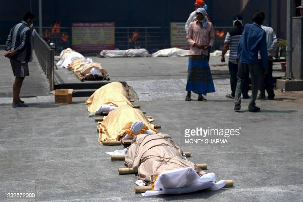 People stand nearbodies of Covid-19 coronavirus victims lined up before cremation at a cremation ground in New Delhi on April 28, 2021.