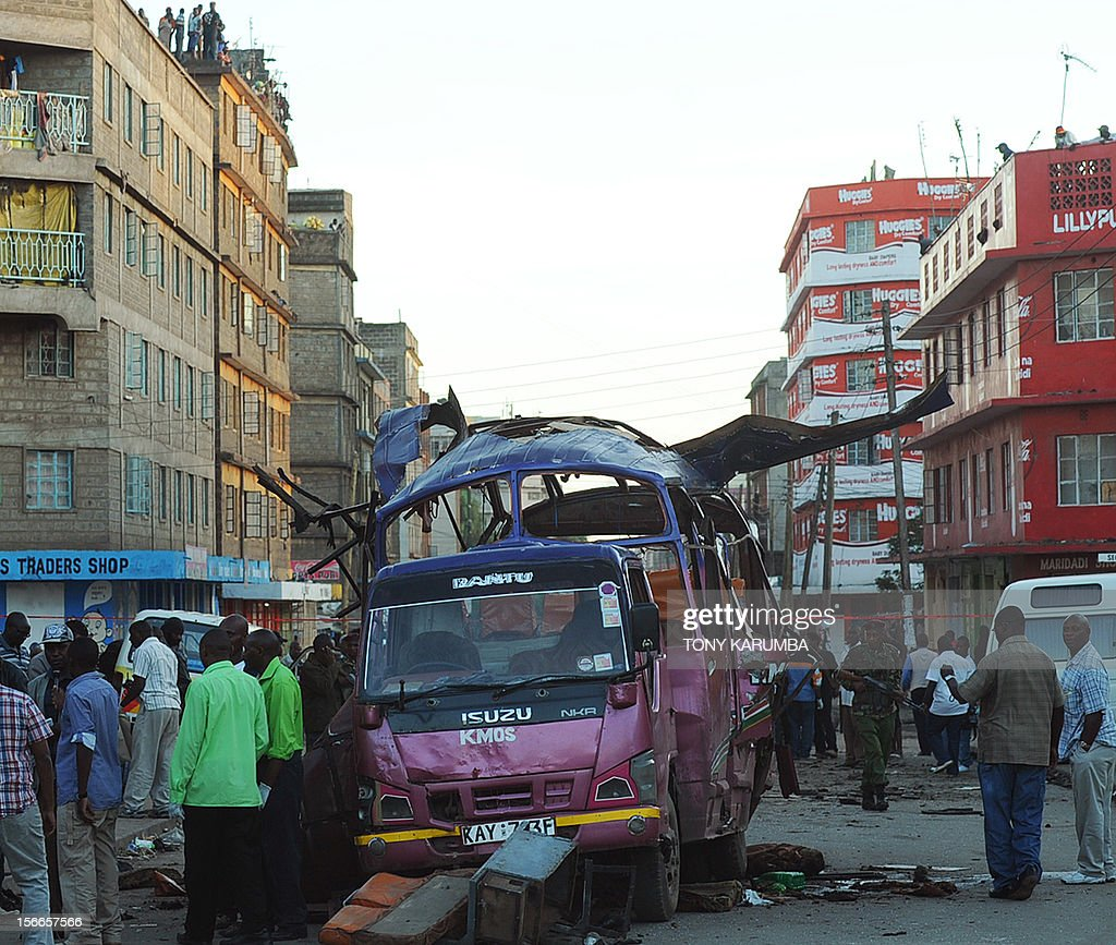 People stand nect to police investigators scrutinizing the scene of a suspected bomb attack in Nairobi's Eastleigh suburb, on November 18, 2012. Seven people were killed and many more wounded when an apparent explosive device was hurled at a packed minibus in a predominantly Somali area of the Kenyan capital Nairobi today, police and the Red Cross said. Nairobi police chief Moses Nyakwama said the blast occurred on a so-called 'matatu', or local minibus, in the district of Eastleigh, where mainly Somalis or Kenyans of Somali origin live and which has been the target of other attacks in recent weeks. AFP PHOTO/Tony KARUMBA