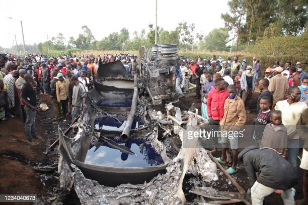 People stand next to a burnt out petrol tanker that burst into flames when it overturned in western Kenya, while a crowd thronged to collect the...