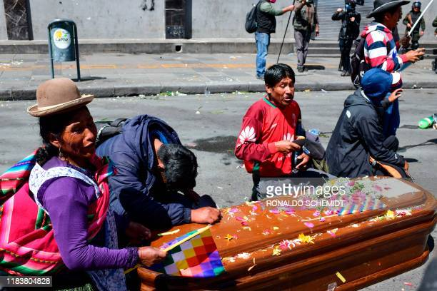 People stand next to a coffin after Bolivian riot police fired tear gas to break up a massive funeral procession that turned into an antigovernment...