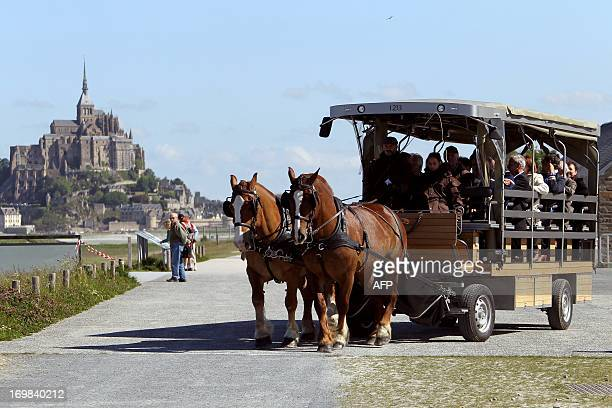 People stand next to a horsedrawn carriage named maringote at the MontSaintMichel French landmark and UNESCO World Heritage site on June 3 2013...