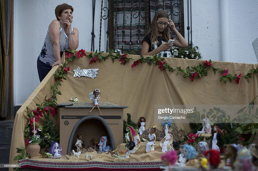 People stand next to a nativity scene made with Monster High dolls during the New Year's Eve in August celebrations on August 2, 2014 in Berchules, Spain. The town of Berchules, located in Granada, on the southern slope of the Sierra Nevada Mountain Range, has had a curious New Year's Eve tradition in place since 1994. The town experienced a power outage on New Year's eve in 1994 and residents were unable to hold the traditional celebrations, so they decided to move their celebrations to the mid-point of the year, holding them in August instead.