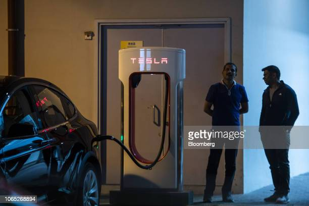 People stand next to a Tesla Inc Model S electric vehicle charging at a Supercharger station inside a parking lot in Hong Kong China on Friday Nov 23...