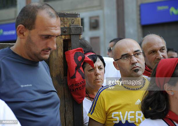 People stand next to a typical San Fermin scraf reading 'Rest in peace' attached to a wooden barrier in a street of Pamplona where a man was gored to...