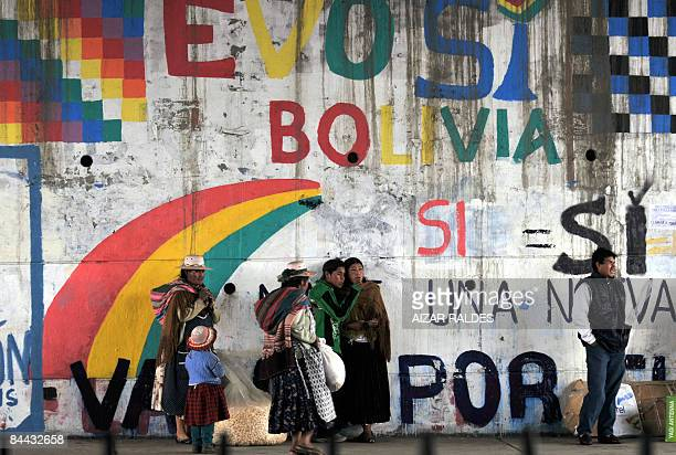 People stand next to a wall with graffitis supporting the new Constitution proposed by Bolivian President Evo Morales in El Alto, on January 23,...