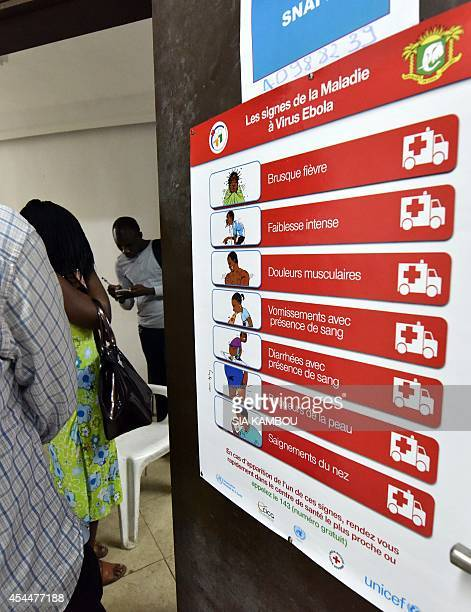 People stand next to an Ebola awareness poster in the Ivorian Popular Front headquarters in Abdijan after it was vandalised on September 1 2014 The...