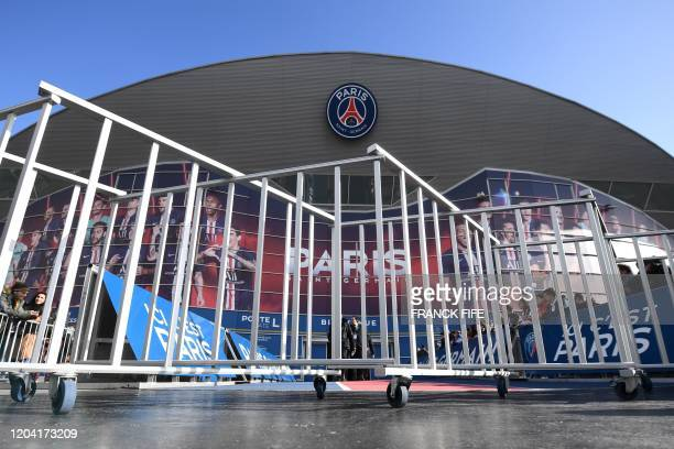 People stand next to barriers set up to prevent contact between players and supporters amid fear of Covid-19 at the Parc des Princes stadium in...